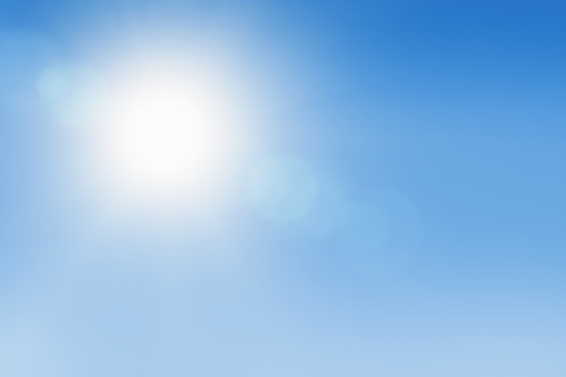 Outdoor background of a white-hot sun overhead in a clear blue sky.